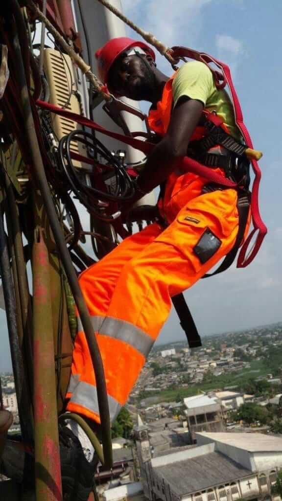 Technicien SMART au sommet d'un pylône entrain de faire une installation des équipements OUTDOOR 2G, 3G et 4G.